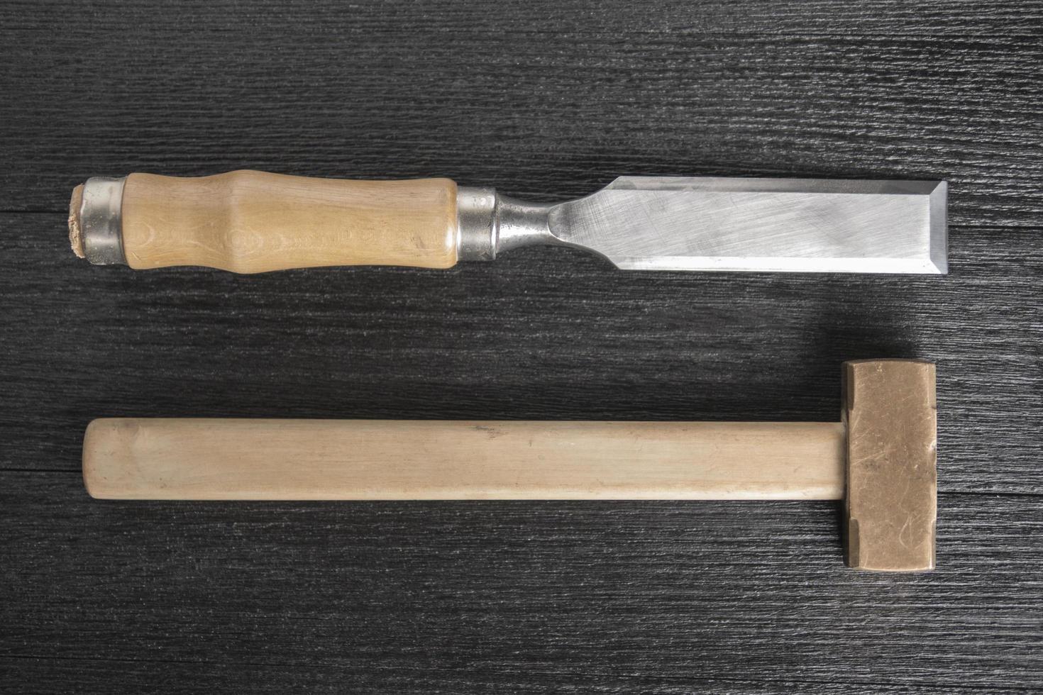 Mazo de cincel y bronce sobre un fondo negro taller de carpintería foto