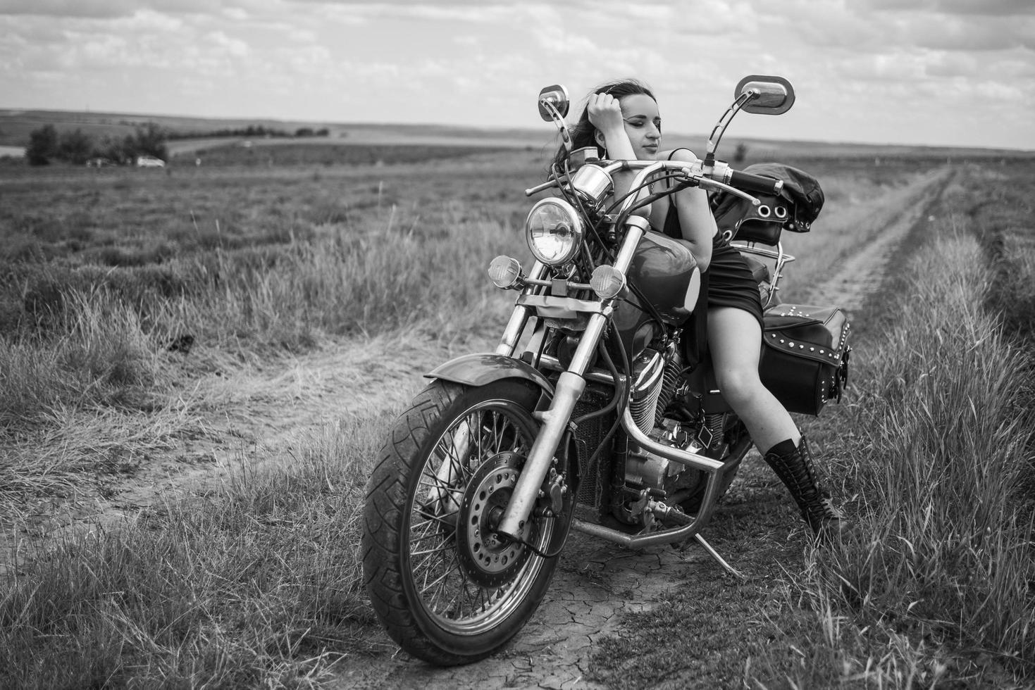 Morena ciclista en una motocicleta en la chaqueta de cuero negro campo lavanda contra el cielo con nubes foto