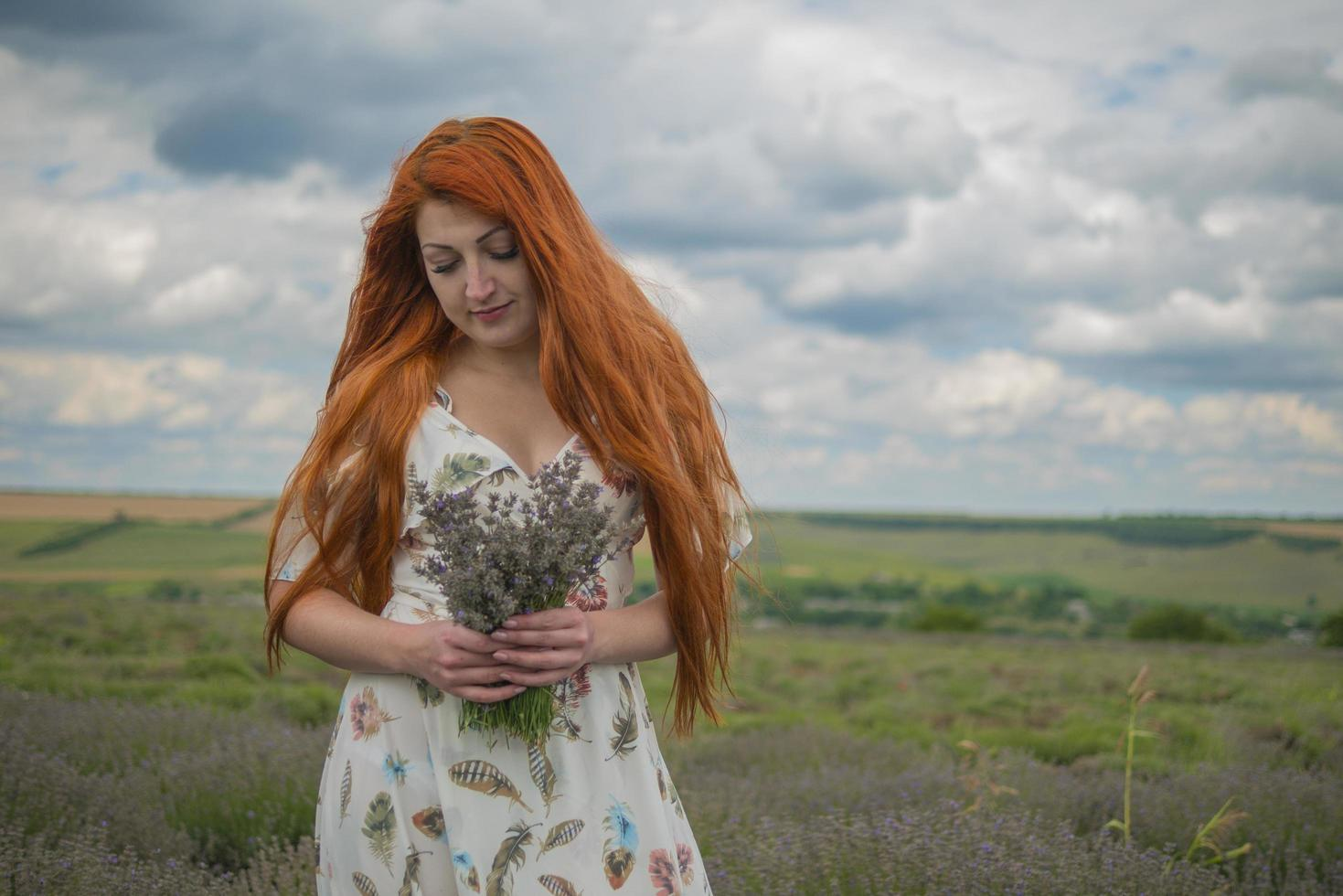 Retrato de una joven pelirroja con un vestido blanco en un campo con un ramo de lavanda foto