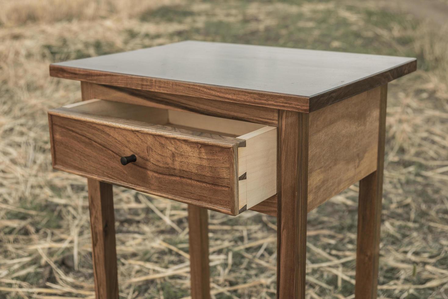 una mesa auxiliar de nogal en un campo de trigo en cola de milano foto