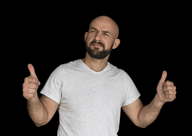 hombre calvo blanco con barba con una camiseta blanca mantiene los dedos en alto foto