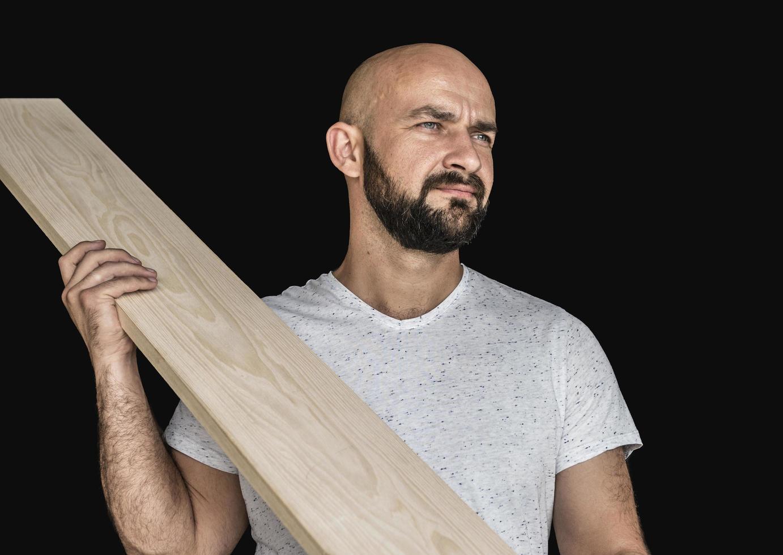 Un carpintero con una camiseta blanca con una tabla preparada mirando hacia otro lado sobre un fondo negro aislar foto