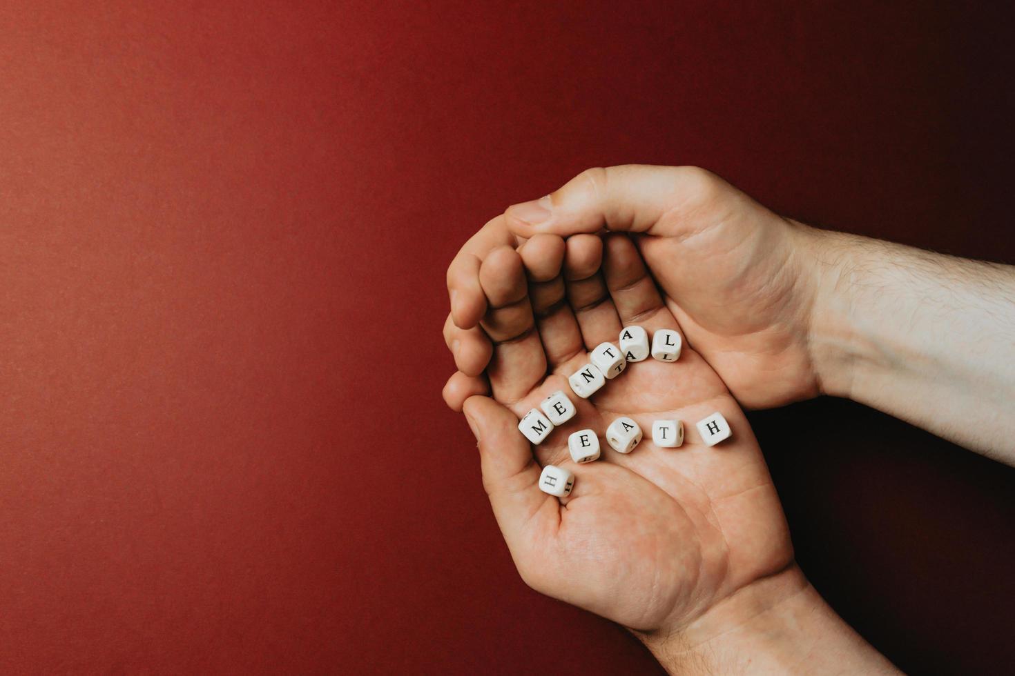 Manos sosteniendo las palabras salud mental sobre un fondo rojo oscuro foto