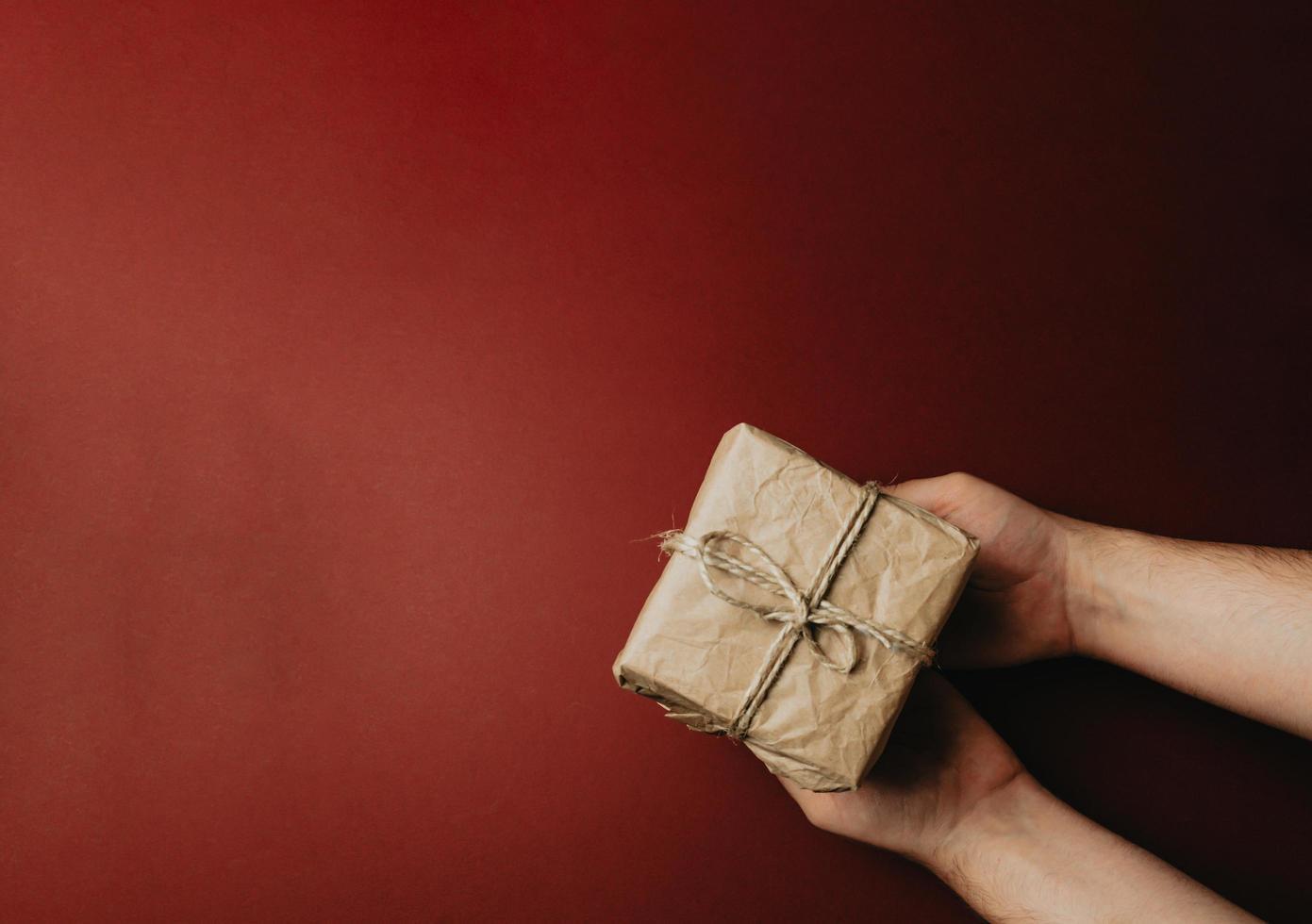 Dos manos dando un regalo sobre un fondo rojo oscuro con espacio de copia foto