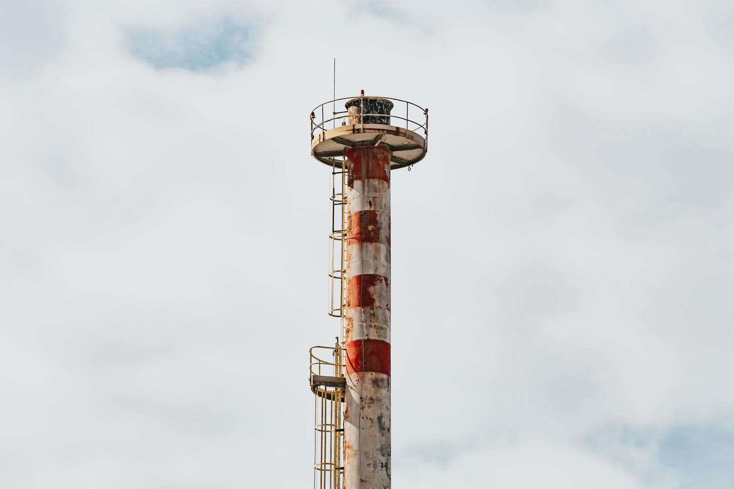 Primer plano de la chimenea de la fábrica con un cielo brillante foto