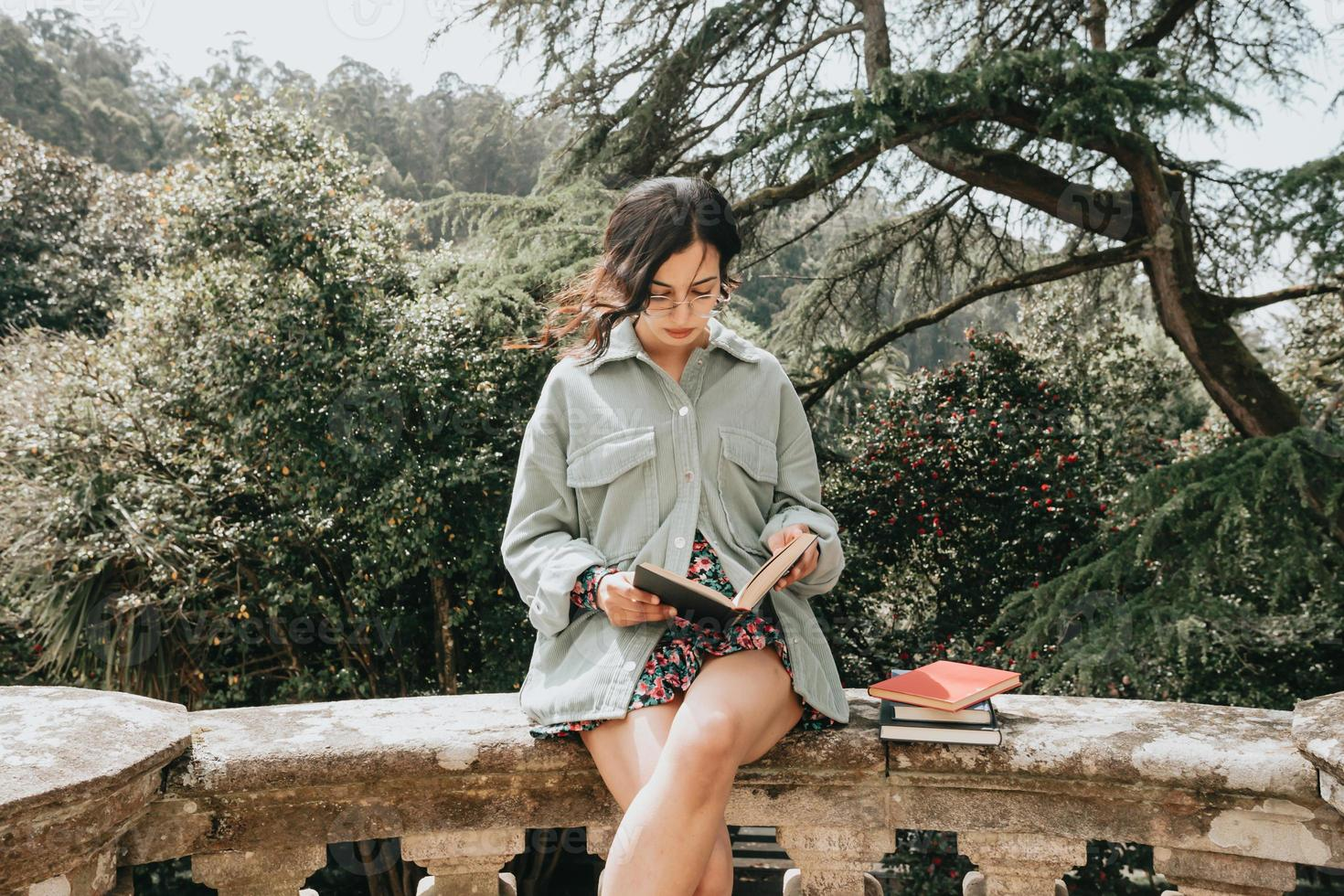 Mujer joven sentada en un edificio antiguo leyendo un libro durante un día soleado foto
