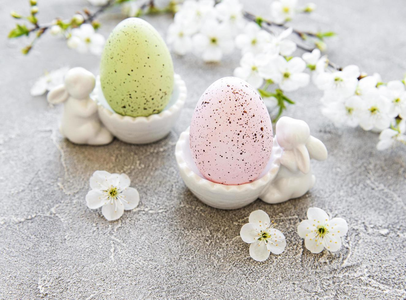 Colorful Easter eggs in a stand with ceramic Easter bunny figurines and spring blossom on gray concrete background photo
