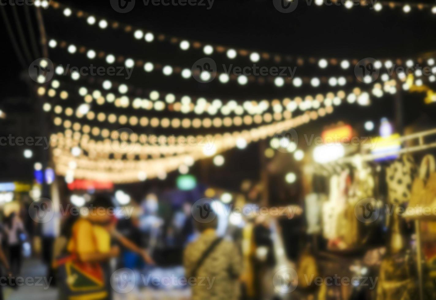 Fondo borroso abstracto de gente de compras en el mercado nocturno de la ciudad foto