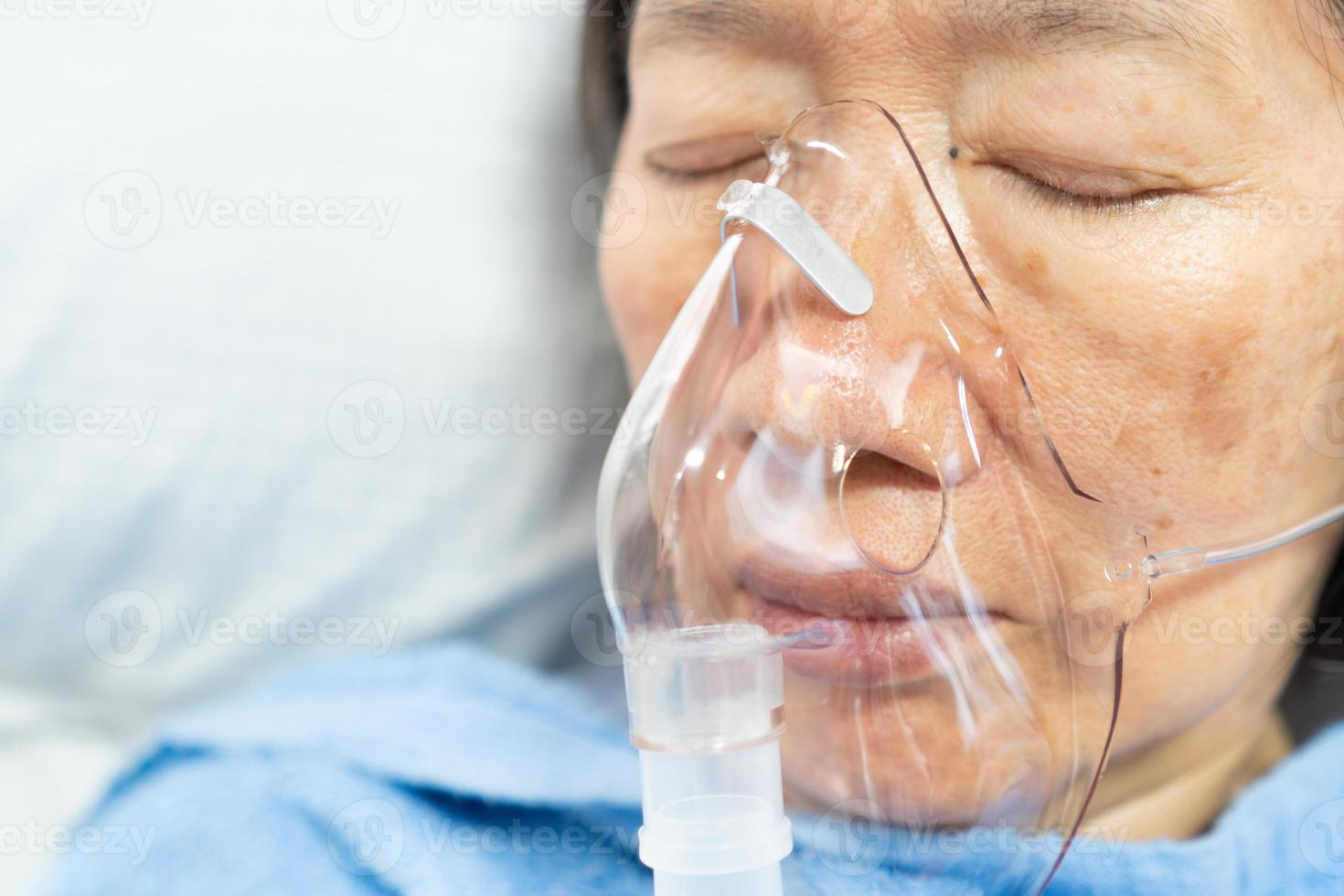 Close up face of senior asian patient having viral pneumonia were treated with oxygen therapy in the hospital photo