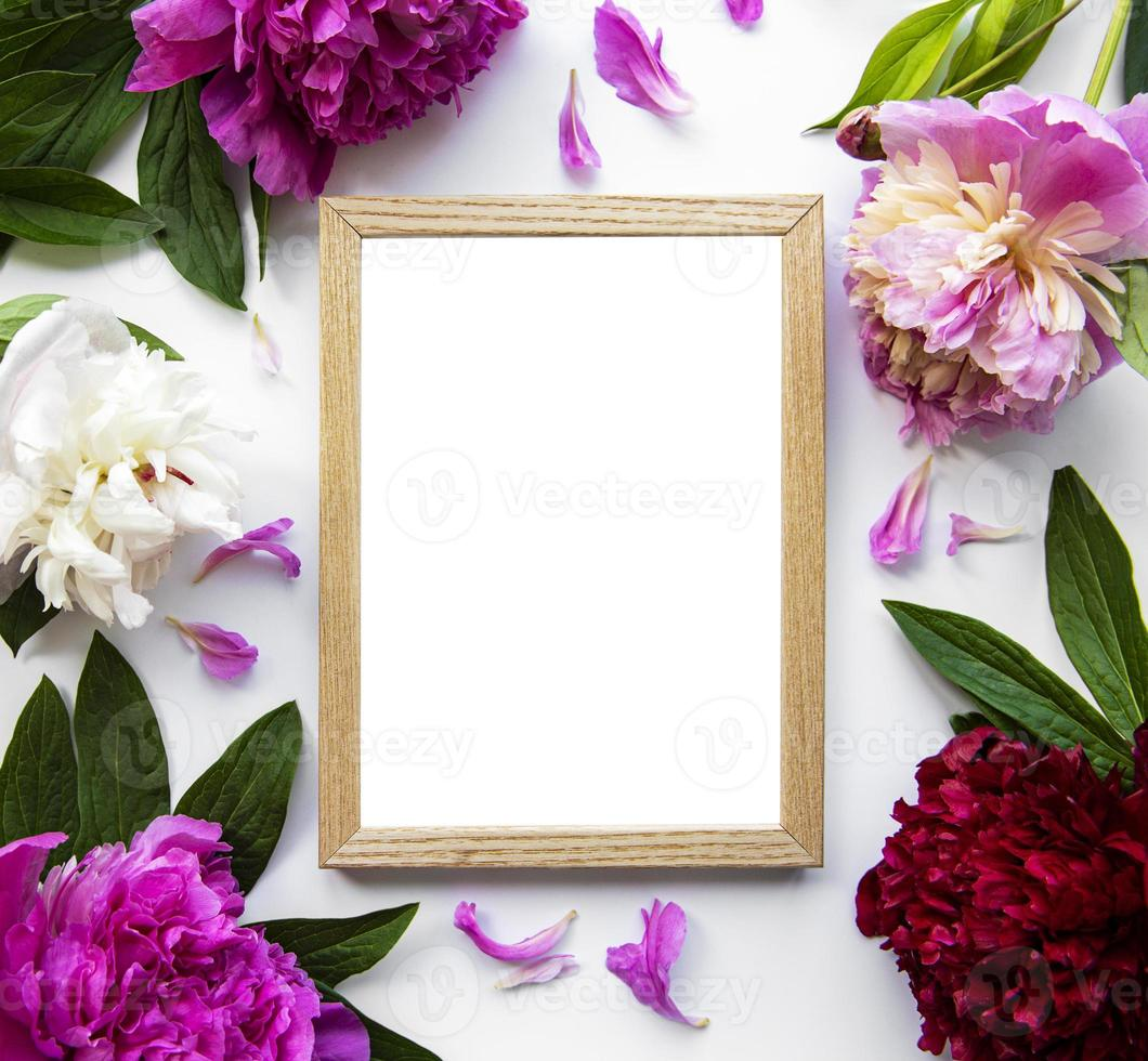 Wooden frame surrounded by beautiful pink peonies on a white background photo