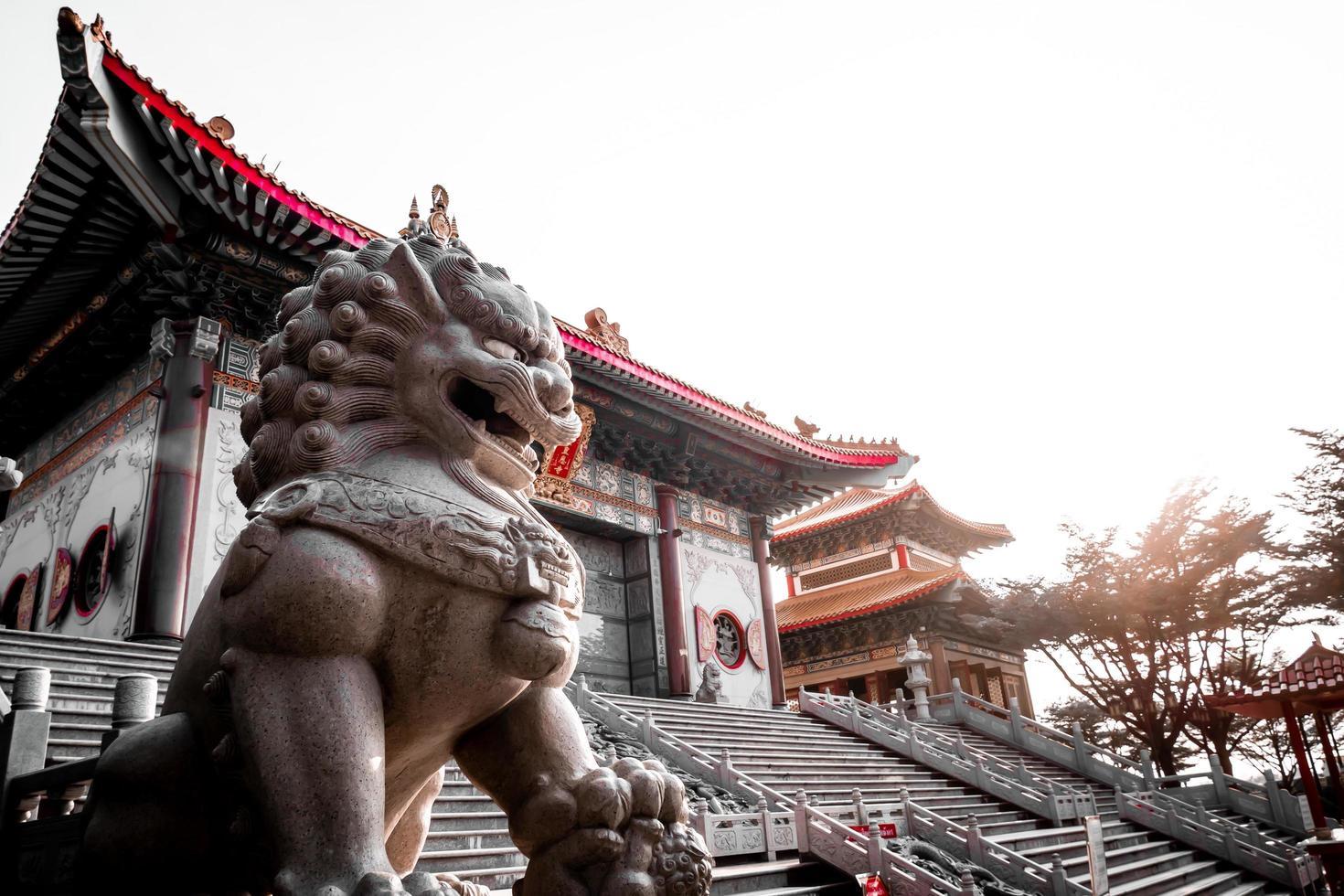 Estatua de piedra de león en el templo chino en Tailandia foto