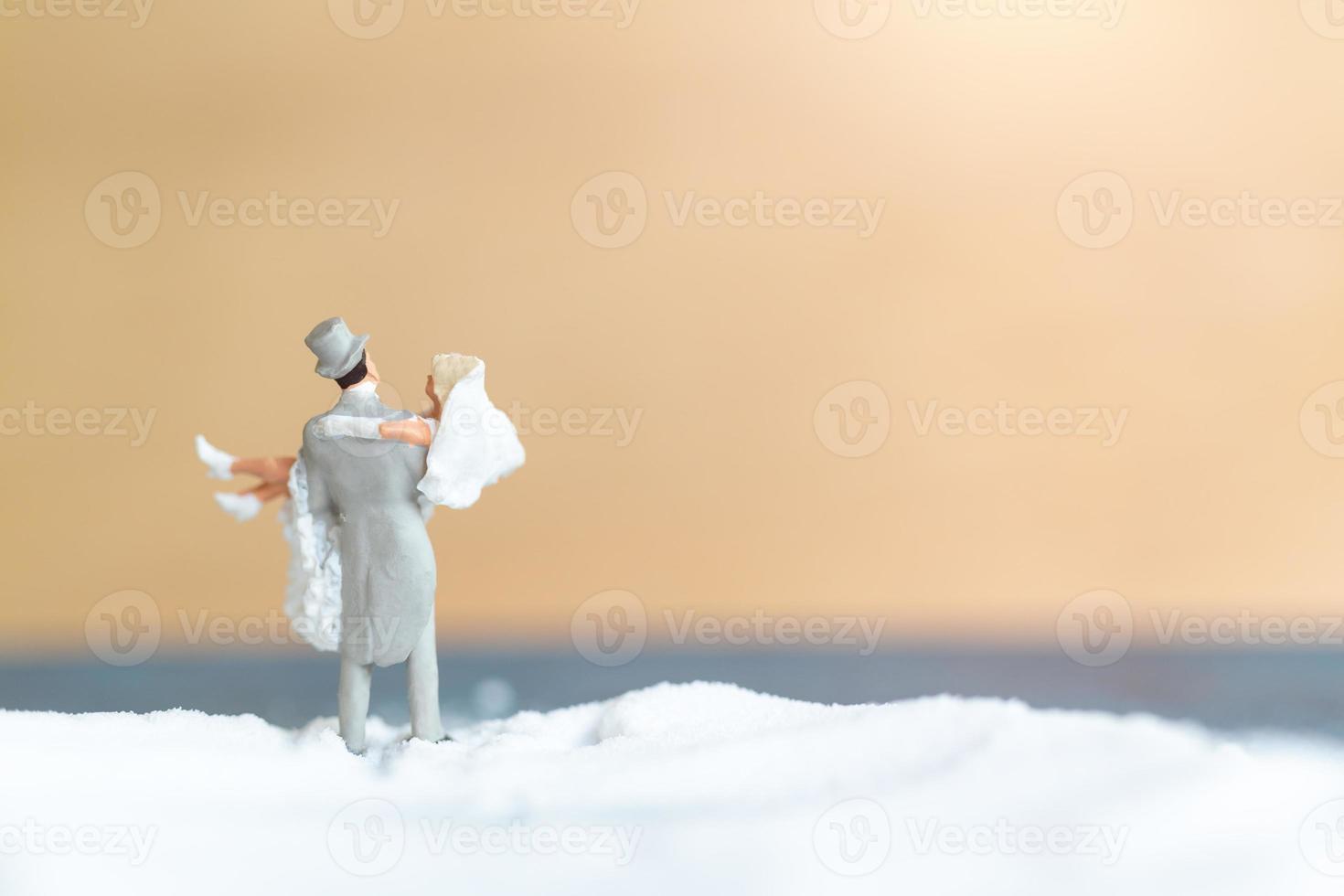 Miniature people, happy wedding couple on a white beach, wedding concept photo