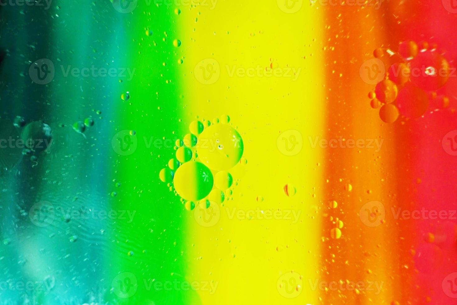 A beautiful and colorful macro of oil bubbles on water with a yellow, red, green, orange and blue stripe texture as background pattern photo