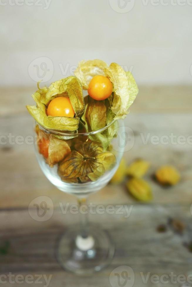 Hermoso y elegante primer plano macro de un lote de fruta sabrosa naranja llamada Physalis de Perú, América del Sur, en un vaso de cristal sobre mesas de madera foto