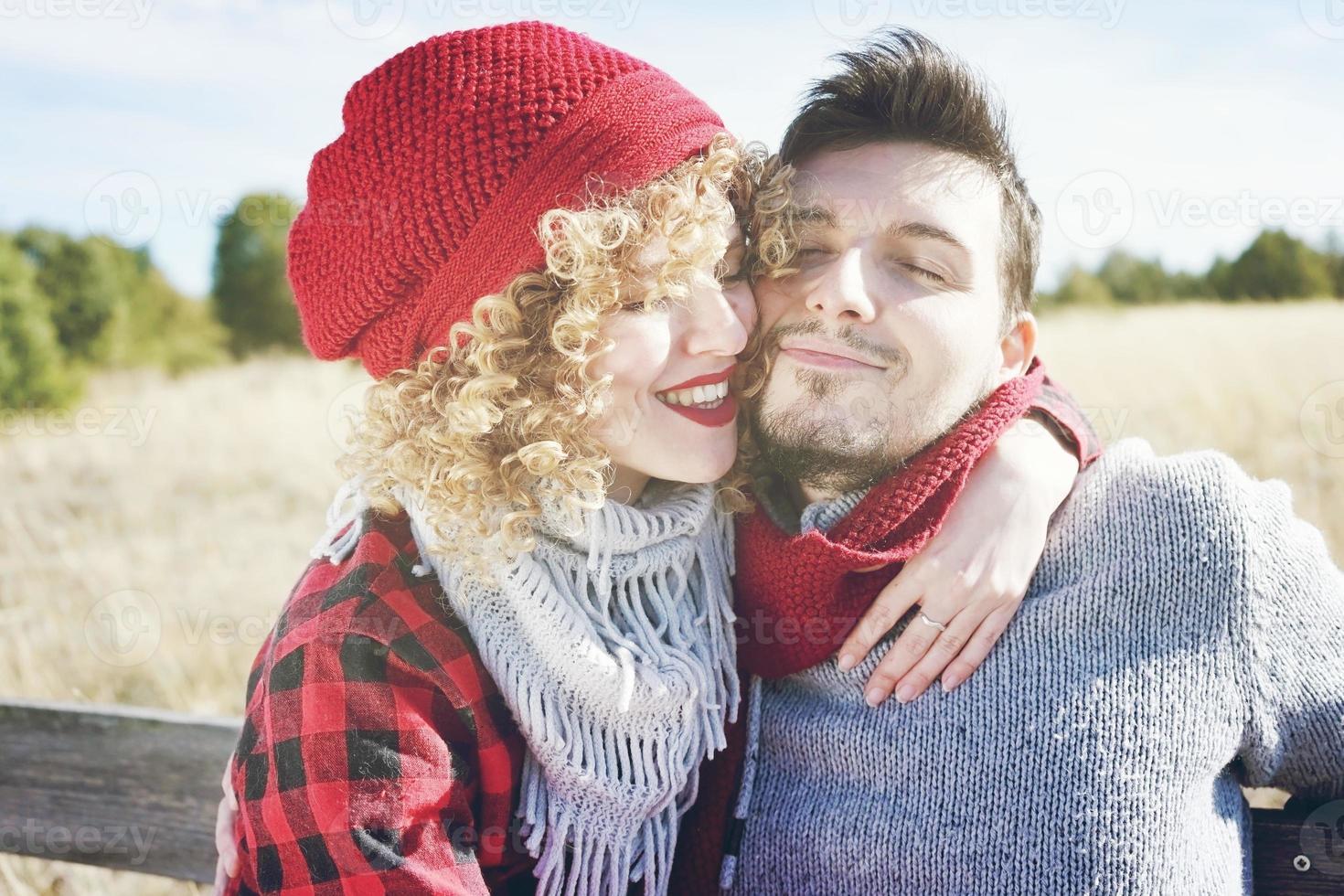 Romántica pareja joven de una hermosa mujer rubia con cabello rizado y con un gorro de lana roja abraza a su novio y un hombre guapo al aire libre foto