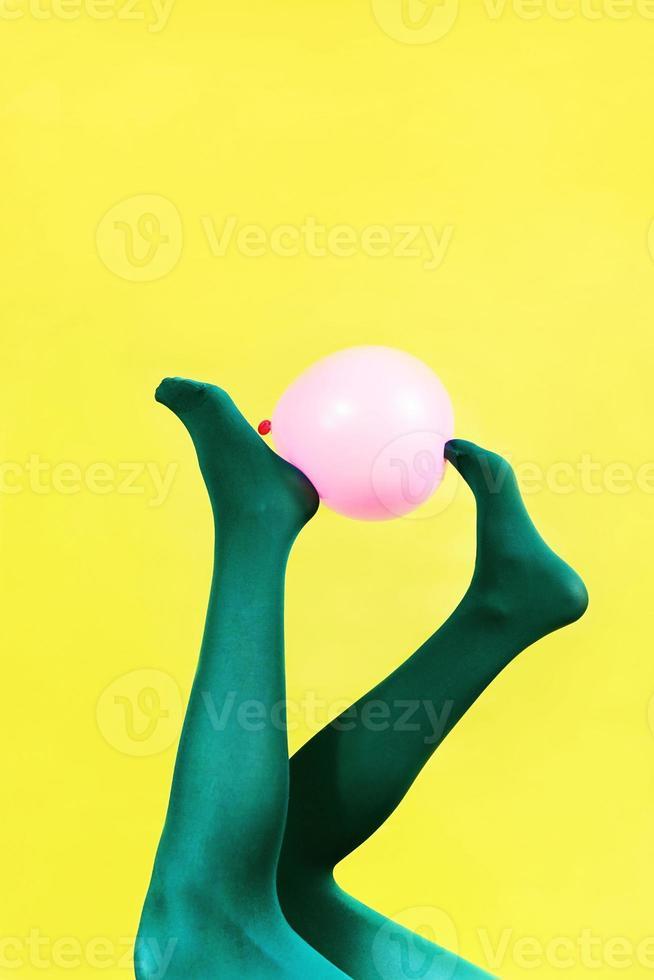 Piernas verdes de una mujer sosteniendo un globo rosa contra una pared amarilla foto