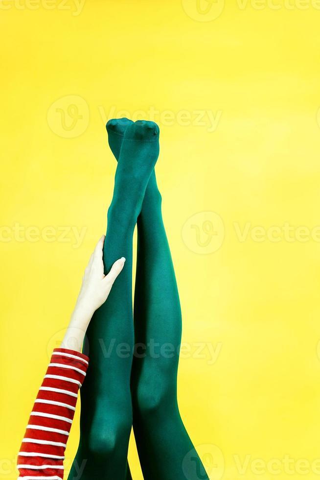 Pieza de arte pop de piernas de mujer joven en mallas sobre un fondo amarillo foto