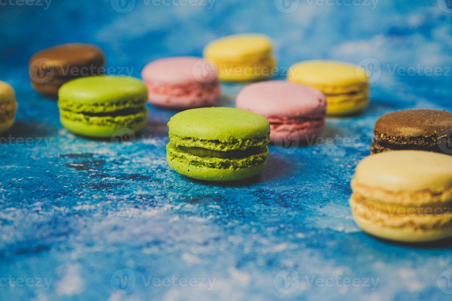 Variedad de macarons de colores sobre un fondo azul. foto