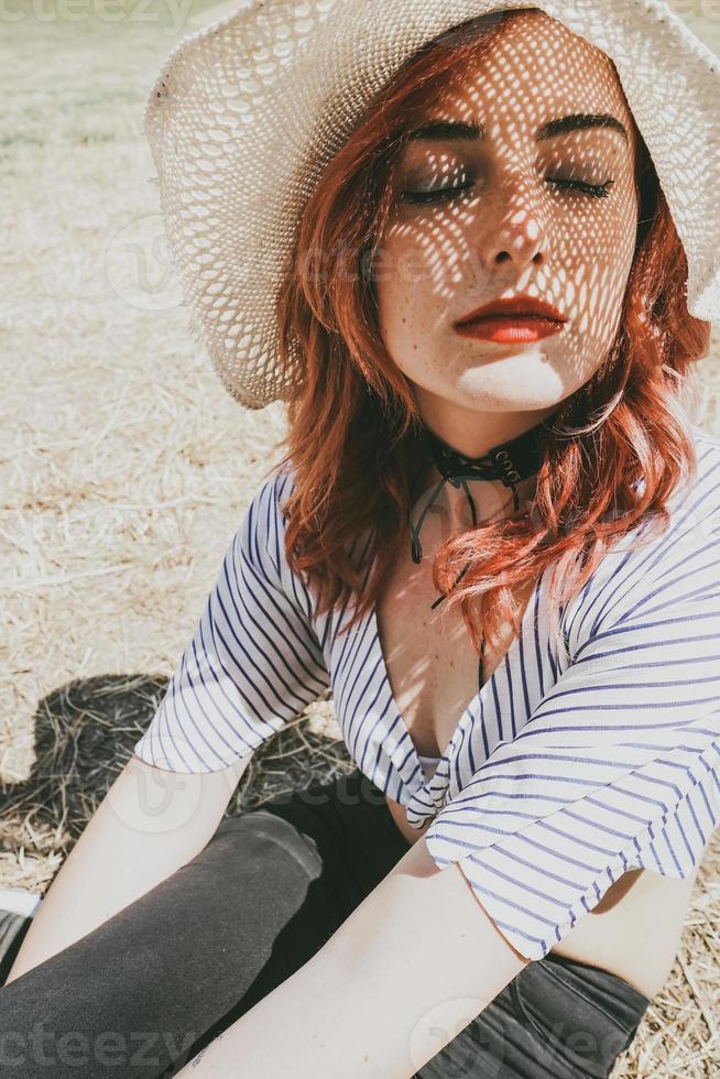 modelo pelirroja protegiéndose del sol con un sombrero en verano foto