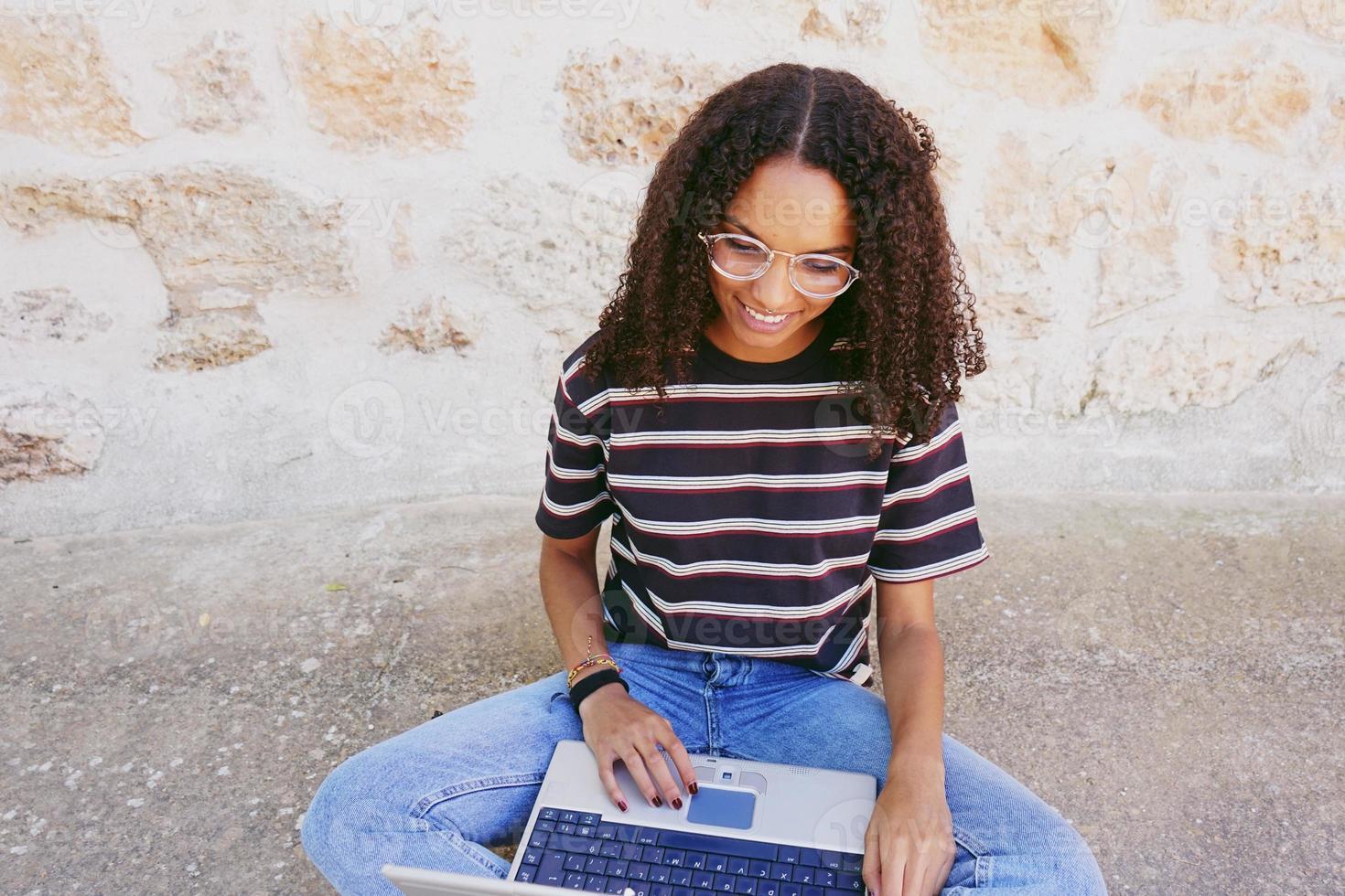 Un retrato de una mujer negra joven y sonriente feliz con el pelo rizado con gafas, jeans y una camiseta a rayas, sentada en el suelo y trabajando o haciendo la tarea foto
