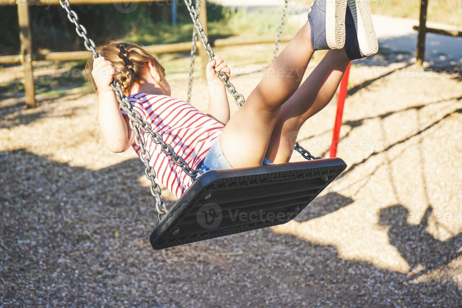 niña joven en un columpio en el parque foto