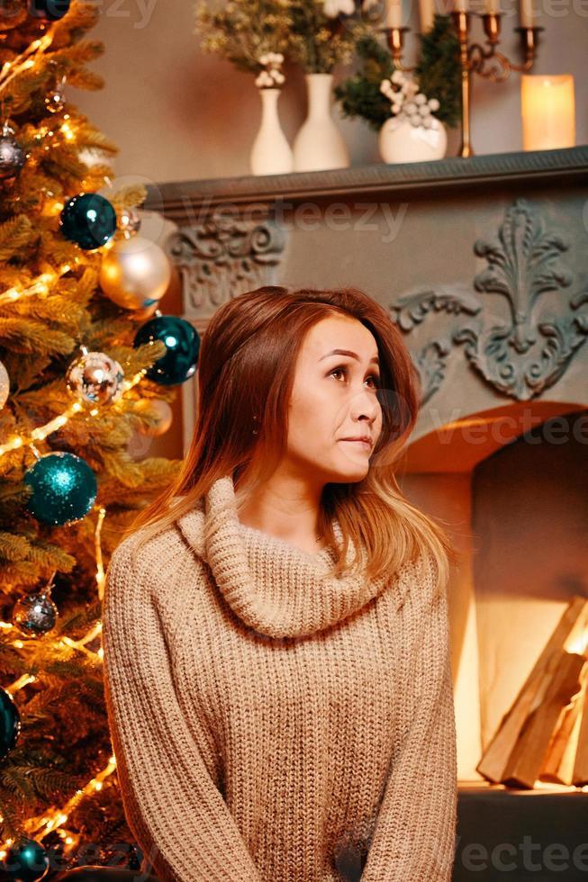 Cute girl among Christmas decorations looks up. photo