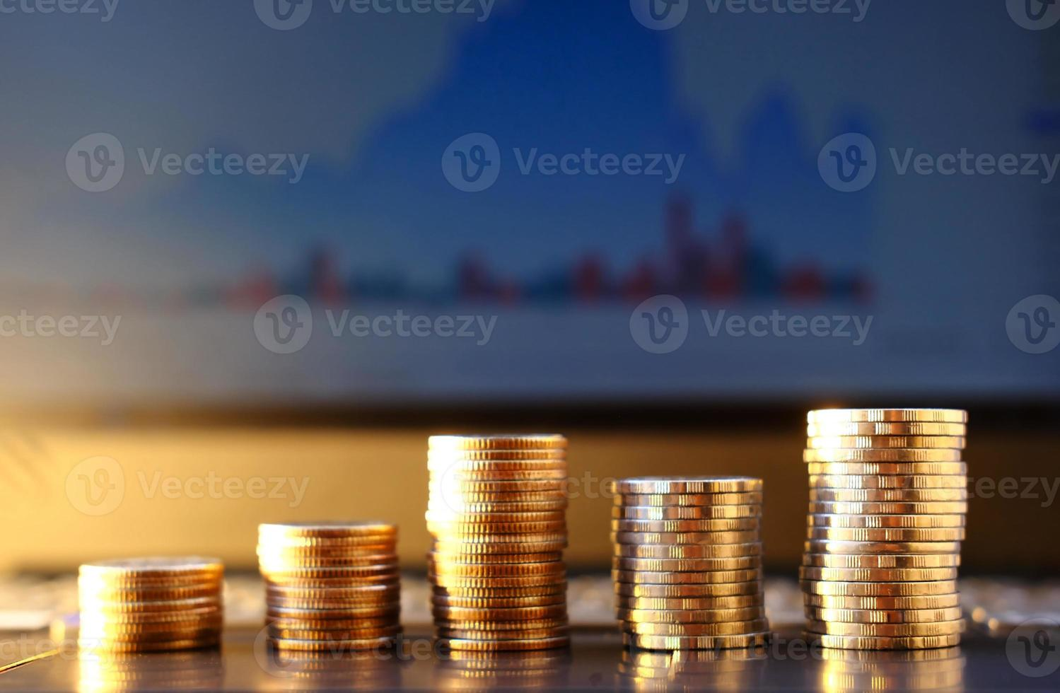 Stack of coin on laptop and graph background and saving money and business growth concept photo