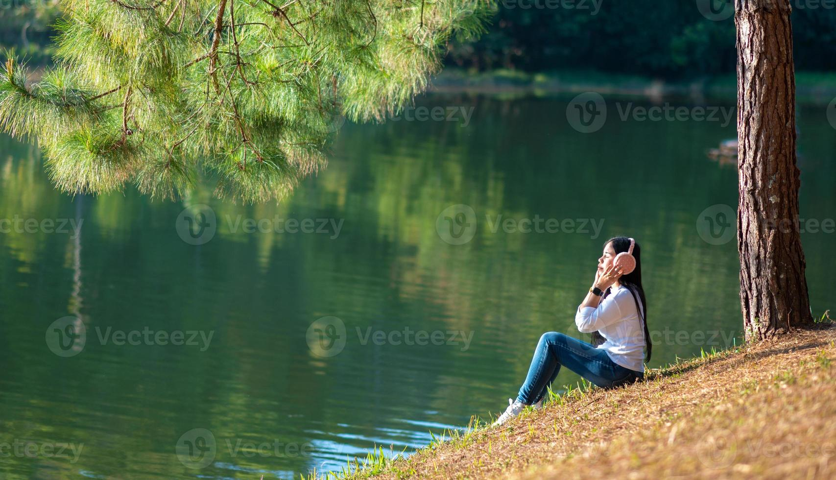 Young people are happily listening to music in their headphones in the midst of nature and the warm light of the morning. photo