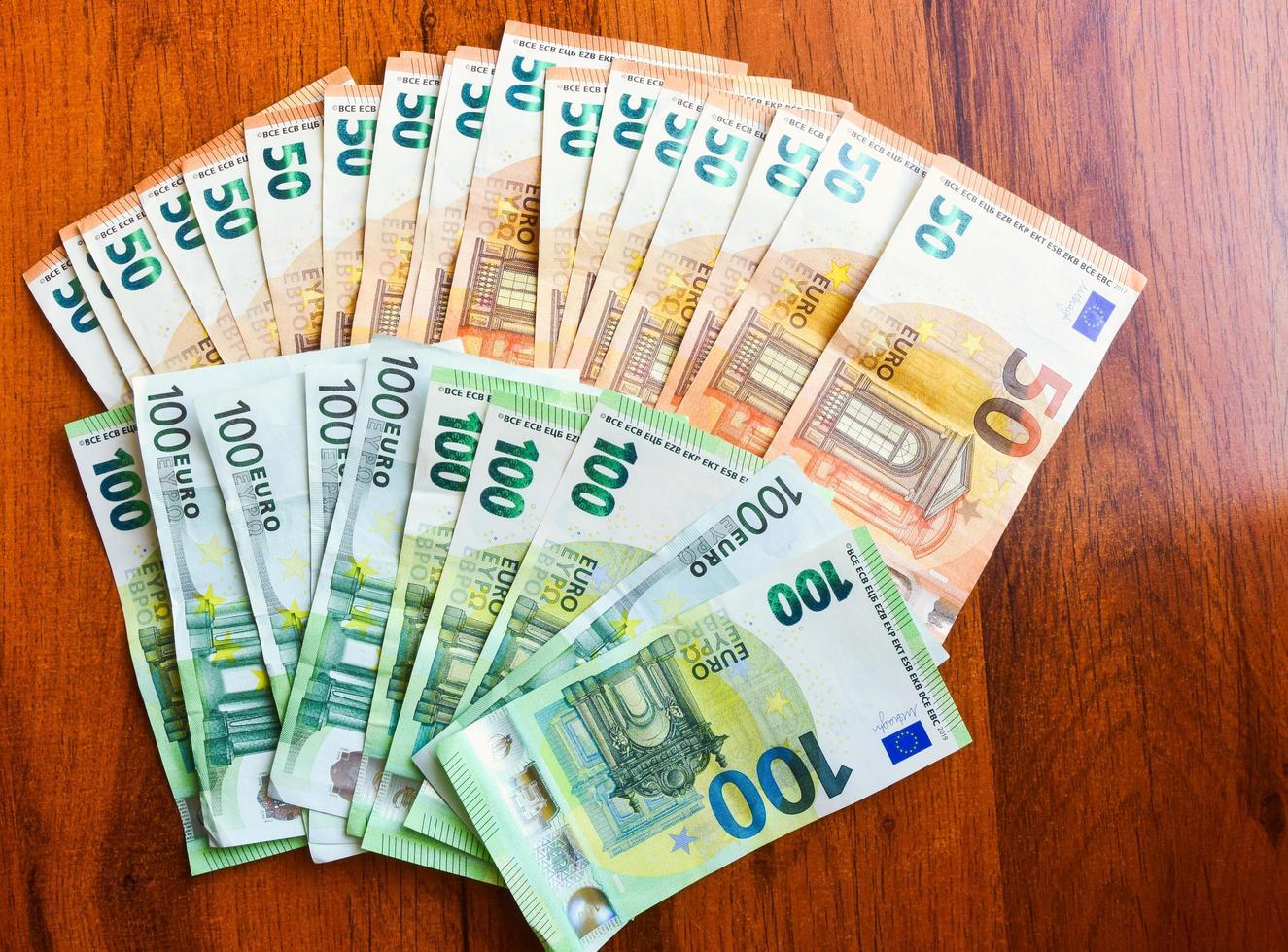 Dos mil euros repartidos en la vista superior del fondo de la mesa de madera foto