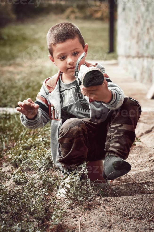 Boy remove sand from his shoe. Young boy trying to remove sand from his shoe. photo