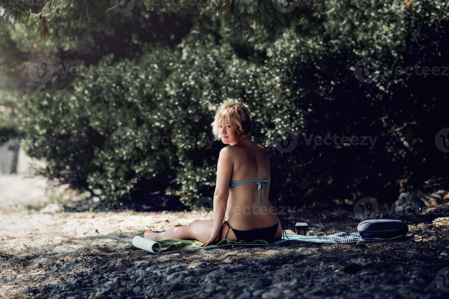 Woman in bikini enjoying alone at the beach. Blonde woman enjoying her coffee in the shade of pine tree at the wild beach. photo