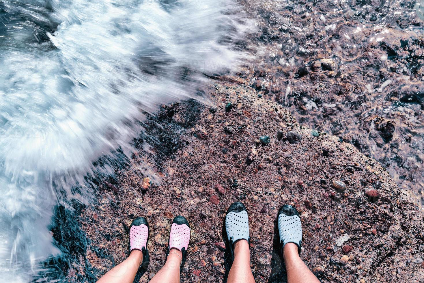 Couple standing together on the stone shore. Feet of couple covered by water wave at the seaside. photo