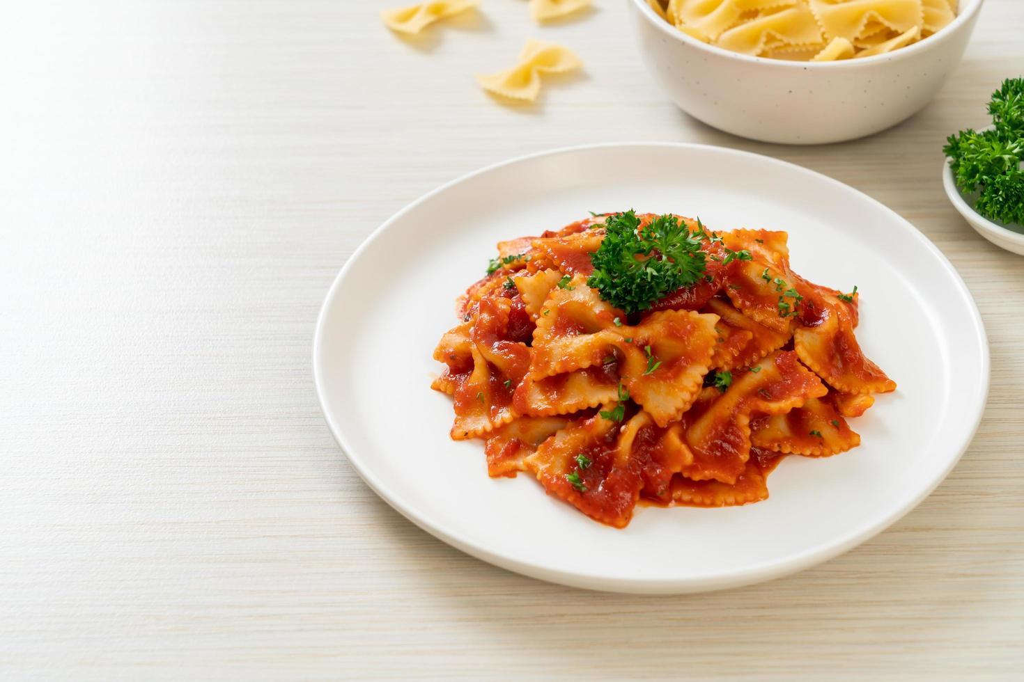 Farfalle pasta in tomato sauce with parsley - Italian food style photo