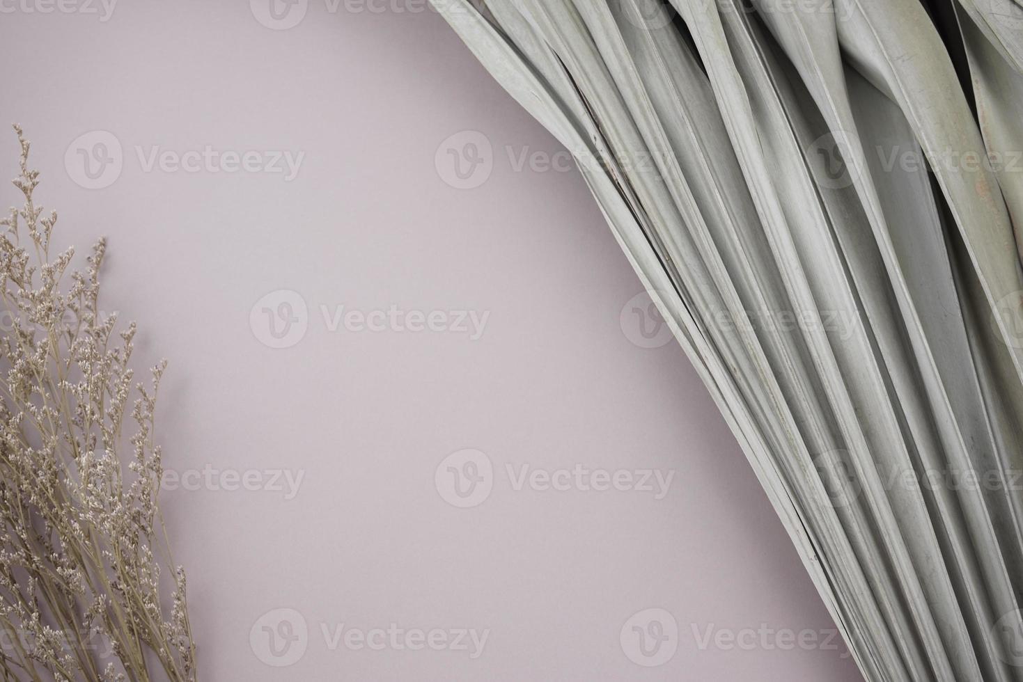 hojas de palma secas y flores marchitas y tupidas bouquet sobre fondo plateado neutro, gris-púrpura pastel. foto