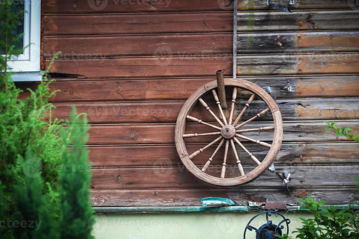 Gran rueda de madera antigua colgada en la pared de tablones de madera de una casa rural foto