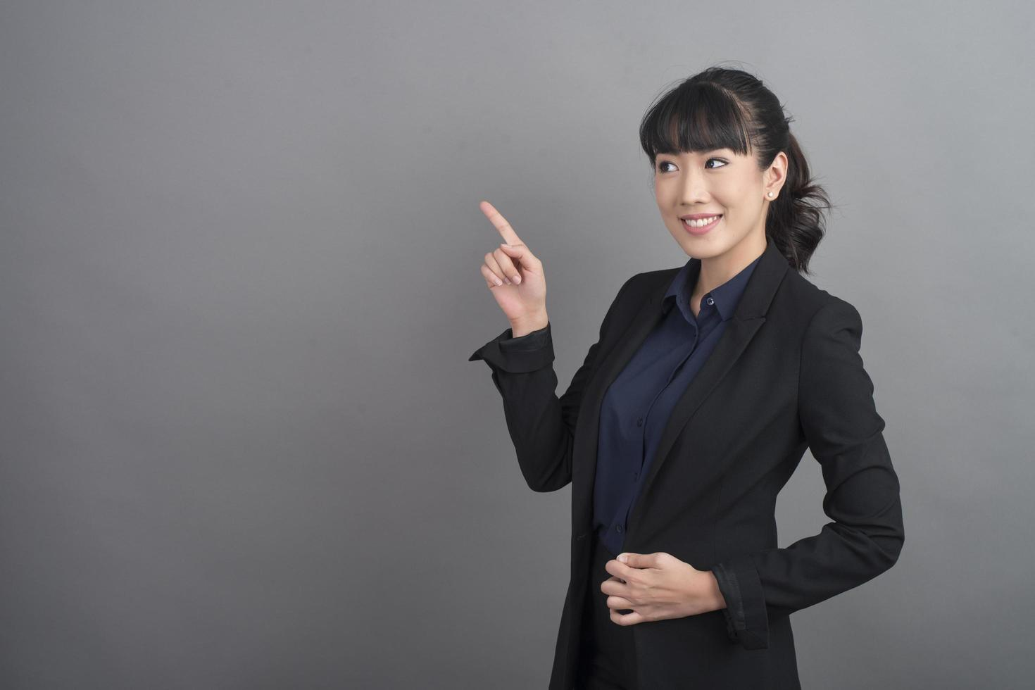 Smiling business woman in blazer on grey background photo
