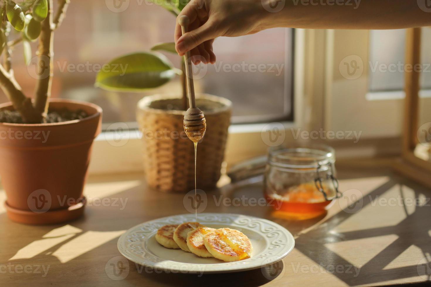 tartas de queso o syrniki en un plato con miel, al fondo un tarro con miel y ficus. una mujer vertiendo una cuchara de madera para la miel que fluye miel. de cerca. enfoque selectivo foto
