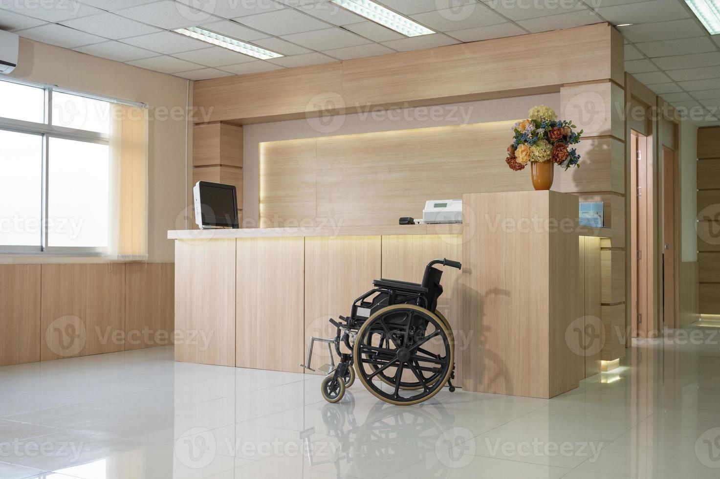 Mostrador de recepción de madera moderno vacío con monitor y silla de ruedas en el hospital foto