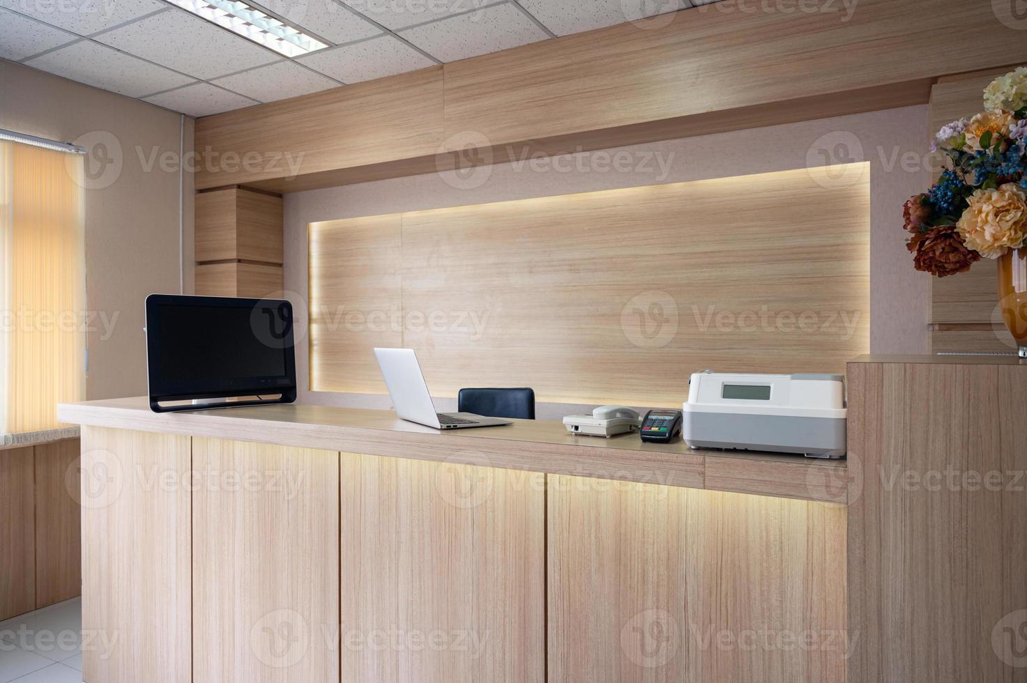 Mostrador de recepción de madera moderna con monitor, portátil y dispositivo electrónico en el hospital foto
