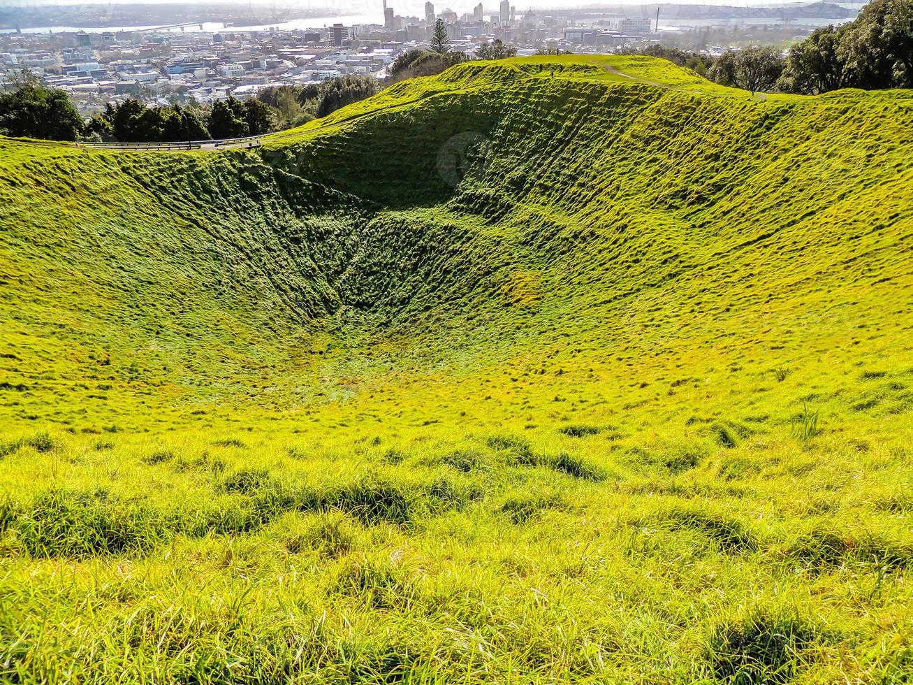 Grass covers the Mount Eden crater, Auckland, New Zealand photo