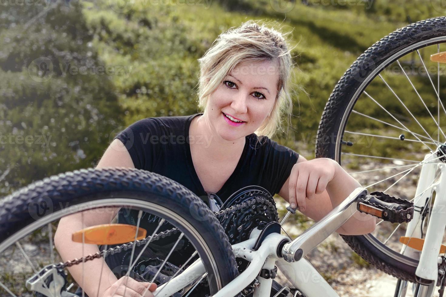 mujer reparar su bicicleta foto