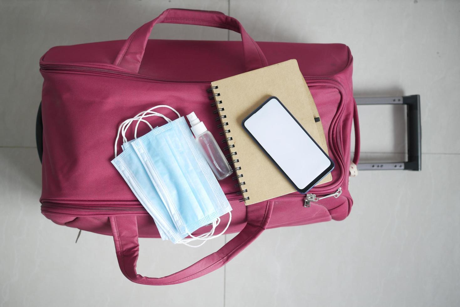 teléfono inteligente, pasaporte, desinfectante de manos y mascarilla en la maleta en el suelo foto
