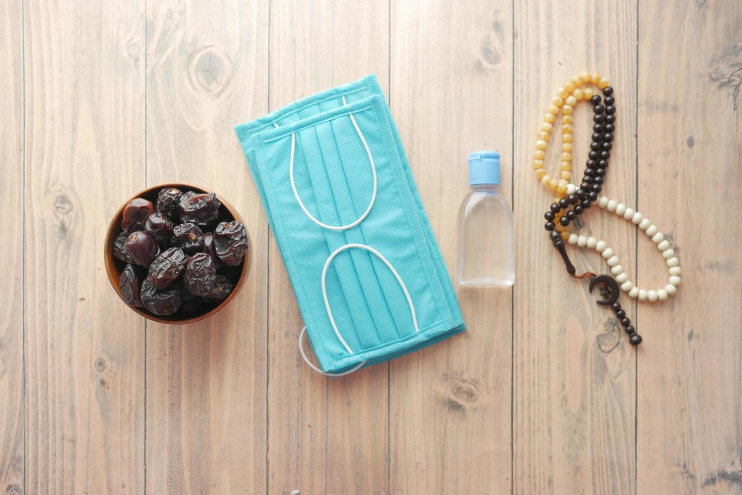 fruta fresca de dátil en un tazón, rosario de oración, desinfectante de manos y mascarilla en el piso foto