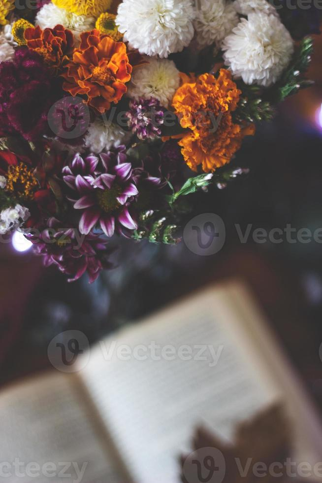 Top view of a bouquet of flowers and open book on the table photo
