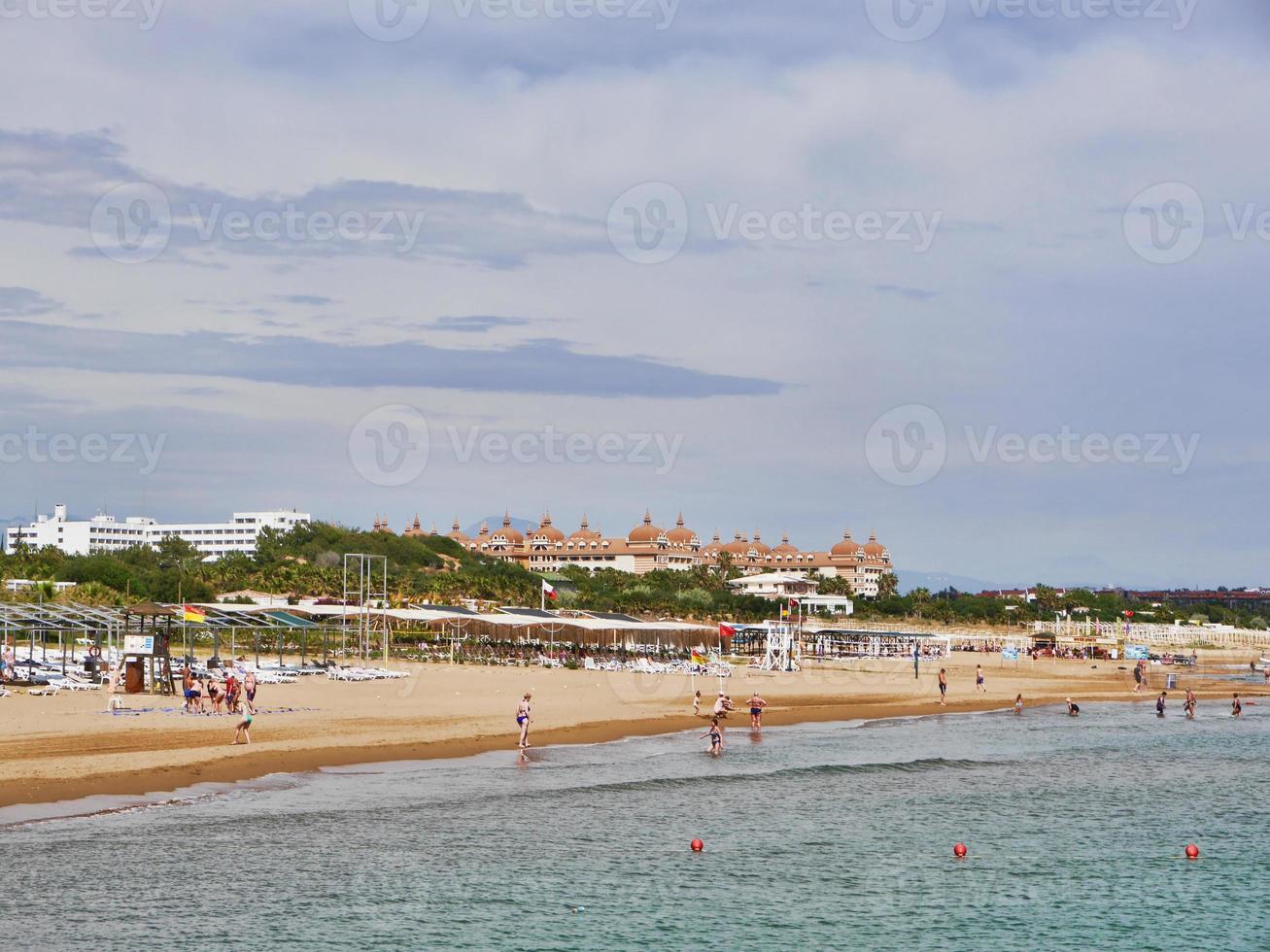 Turkish beach and big hotels on the background. Antalya city, Turkey. May 2017 photo