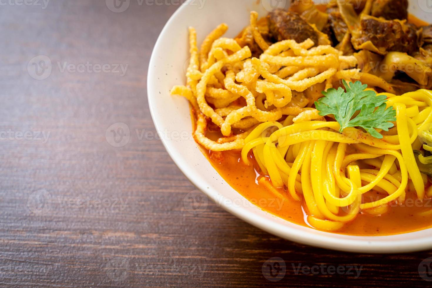 Northern Thai noodle curry soup with braised pork photo