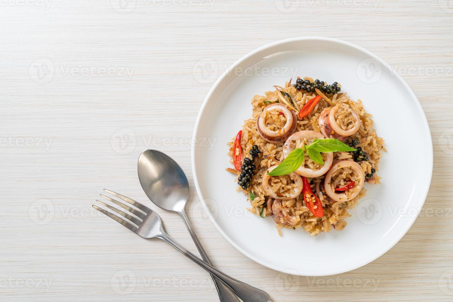 Arroz frito con albahaca y hierbas picantes con calamar o pulpo foto