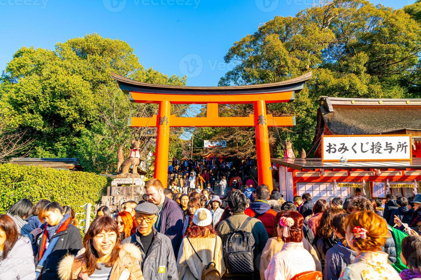 kyoto, japón - 11 de enero de 2020 - puertas torii rojas en fushimi inari taisha con turistas y estudiantes japoneses. fushimi inari es el santuario sintoísta más importante. foto