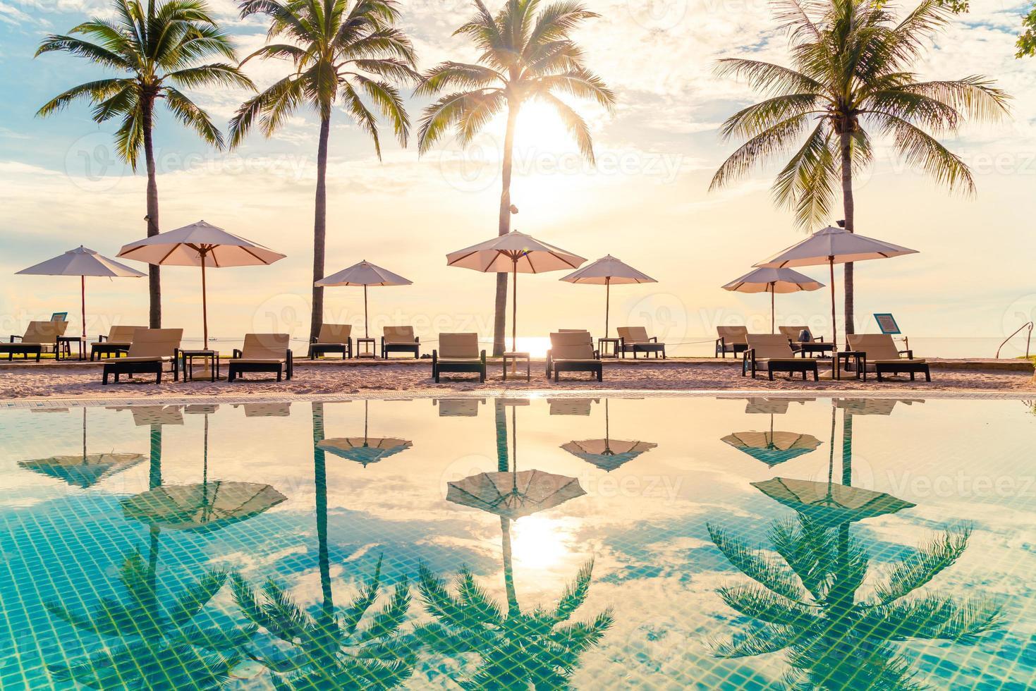Hermosa sombrilla de lujo y una silla alrededor de la piscina al aire libre en el hotel y resort con palmera de coco en el cielo al atardecer o al amanecer foto