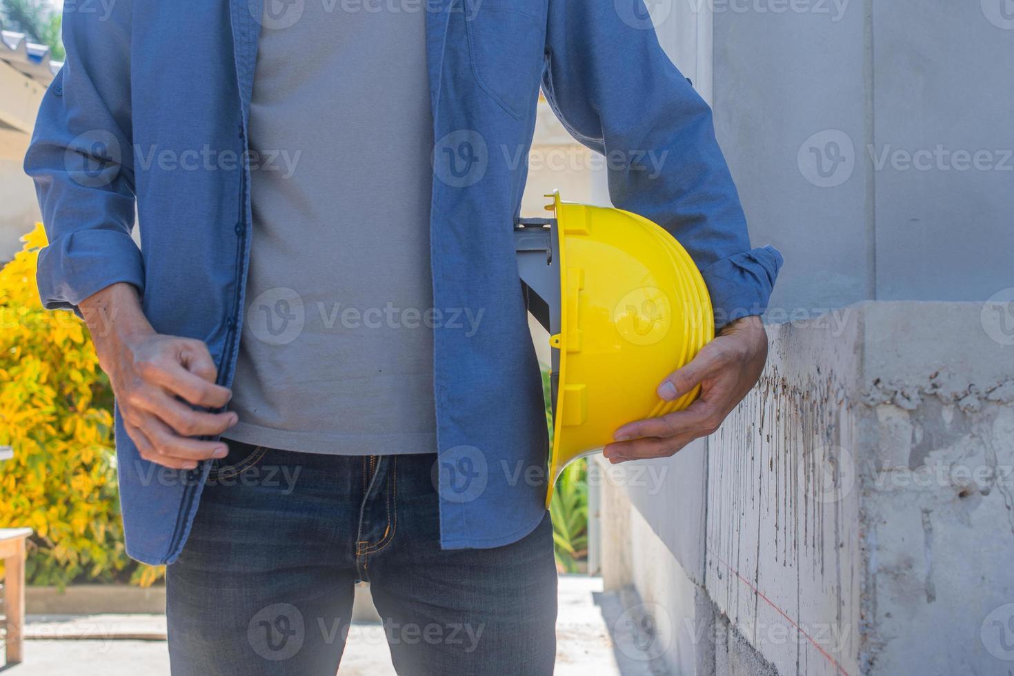 Trabajador arquitecto sosteniendo casco amarillo en la construcción de edificios foto